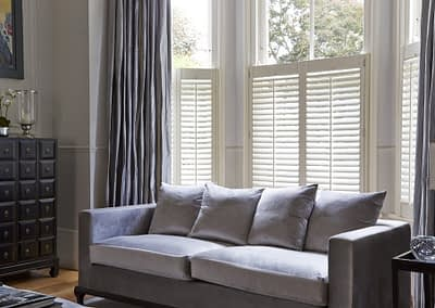 Café style shutters cover the lower portion of the window only.